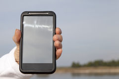 Hand showing smart mobile phone with blank screen Royalty Free Stock Photo