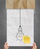 Hand showing sticky note with another idea light bulb on crumple Stock Photo