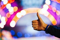Hand showing thumbs great sign on natural bokeh blurred abstract background.  Royalty Free Stock Photo