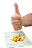 Hand showing thumbs up above a medical prescription. White male's hand showing thumbs up above a medical prescription with some pills on it Royalty Free Stock Photography