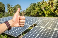 Hand showing Thumbs Up By the backdrop is solar energy. stock image