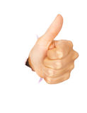 Hand showing thumbs-up out of torn hole. In white wall. All on white background royalty free stock image