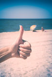 Hand showing thumbs up or shows good. Instagram stylisation. Close-up picture of woman`s hand showing thumbs up or shows good and like on the beach against blue Royalty Free Stock Photography