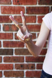 Hand showing victory sign. Hand showing peace sign against a brick wall Royalty Free Stock Image