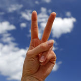 Hand showing victory sign. With blue sky in the background Stock Photo