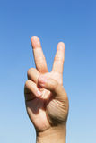 Hand showing victory sign on sky background. Hand showing victory sign on blue sky background Stock Photos