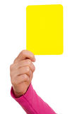 Hand is showing a yellow card. Female hand is showing a yellow card Stock Photos