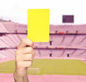 Hand showing a yellow card in front of a stadium Royalty Free Stock Photo