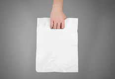 Hand shows blank plastic bag mock up isolated. Empty white polyethylene package mockup. Consumer pack ready for logo design or id. Entity presentation royalty free stock photos