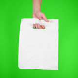 Hand shows blank plastic bag mock up isolated. Empty white polyethylene package mockup. Consumer pack ready for logo design or id. Entity presentation royalty free stock image