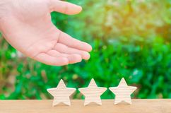 The hand shows the three stasr. The concept of recognition of high quality and good service. Review hotel or cafe. High rating, su royalty free stock images