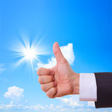 Hand shows thumbs up, Sky and sun Stock Photo