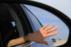 Hand in side view mirror. Woman hand with a ring in the side view car mirror Stock Image