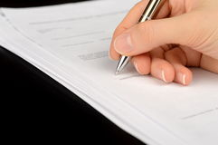 Hand signing a bank account contract. Female hand signing a bank account contract Stock Photo