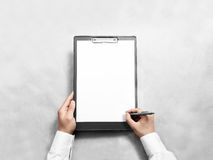 Hand signing blank black clipboard with white a4 paper design mockup. Clear document holder mock up template hold arm. Clip board notepad surface display front Royalty Free Stock Image
