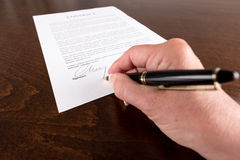 Hand signing a contract Stock Photos