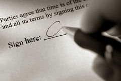 Hand Signing a Document in Ink on Sign Here Line stock images