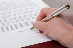 Hand signing a paper Royalty Free Stock Photography