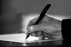 Hand Signing Paperwork/Contract (Black & White). Close-up of a hand at a desk signing paperwork/document/contract or writing communications - Black and White