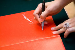 Hand signing on a red guests book Stock Images