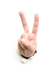 Hand signs. Hand showing victory through the paper hole isolated on white background Stock Photography
