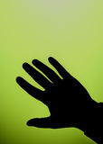 Hand silhouette. Against a graduated green background stock images