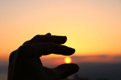 Hand silhouette aginst the sun. Royalty Free Stock Image