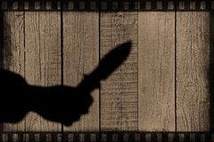 Hand Silhouette with knife on the Natural Wooden Panel Royalty Free Stock Image