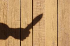 Hand Silhouette with knife on the Natural Wooden Panel Royalty Free Stock Photography