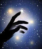 Hand silhouette touching with a finger a star. In the sky Royalty Free Stock Images