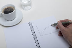 Hand sketch in a notebook. Top view of a hand of a business man drafting a drawing into his notebook or sketchbook using a pencil having a cup of coffee and a Stock Images
