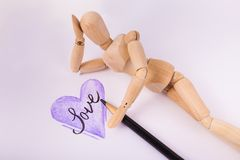 Hand sketched Purple Heart jointed doll laying by heart day dreaming. Hand sketched Purple Heart wooden jointed manikin doll laying daydreaming by heart with stock photography