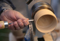 Skilled craftsman with the chisel during the work of the wood pi Royalty Free Stock Photography