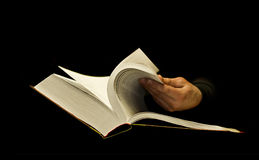 Hand Skimming Thick Book On Black. Hand skimming thick book isolated on black Royalty Free Stock Images