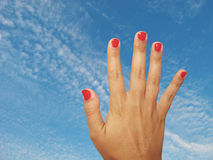 Hand and sky. Female hand with red nails against the sky Royalty Free Stock Photos