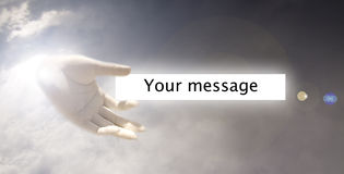 Hand from sky. A view of a hand seeming to come from the clouds in the sky, holding a white strip with a message Stock Photography