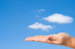 Hand in sky clouds background. Stock Photo