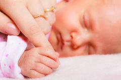 Hand the sleeping baby girl in the palm of mother Royalty Free Stock Image