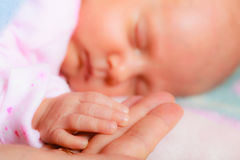 Hand the sleeping baby girl in the palm of mother. Parenting and love concept. Closeup tiny hand the sleeping baby girl in the palm of mother Stock Photo