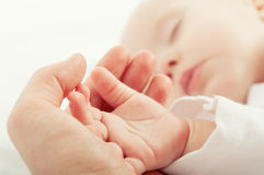 Hand the sleeping baby in the hand of mother Stock Images