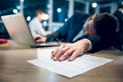 Young businessman sleeping on table. Hand of sleeping businessman lying on pile of papers. Exhausted young guy sleeping on a desk after working on laptop in his Royalty Free Stock Images