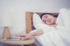 Hand of sleepy woman waking up with alarm clock on mobile phone in bedroom. royalty free stock photography