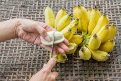Hand slice banana on basket. Stock Photo