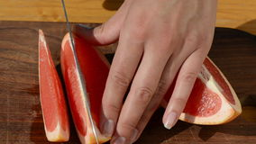 Hand slice fresh ripe juicy grapefruit pomelo fruit into pieces stock video footage