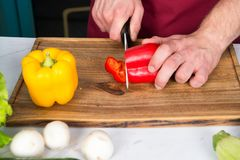 Hand slice pepper with ceramic knife. Vegetables getting cut on wooden cutting board. Food preparation and cooking recipes. Vegeta. Rian menu and healthy diet royalty free stock photo