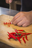 Hand slicing Chilli pepper with Knife on chopping board on woode. N background Stock Images