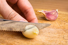 Hand slicing garlic Stock Photos