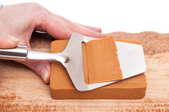 Hand is slicing a piece of cheese Royalty Free Stock Photos
