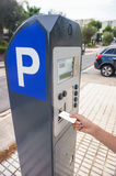 Hand is slipping curd into parking meter Royalty Free Stock Images