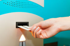 Hand is slipping parking ticket into pay machine. Close-up Stock Images